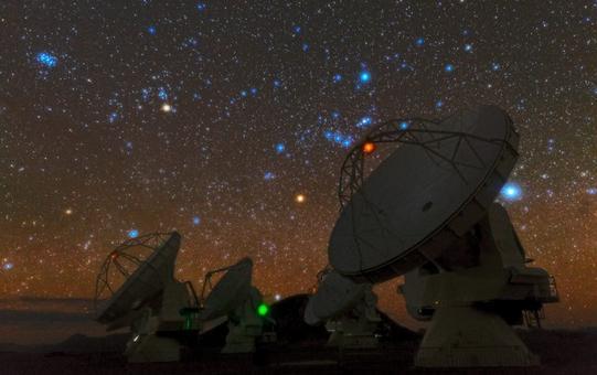 Gas e nuove stelle: costellazione di Orione (centro-destra) e ammasso delle Pleiadi (alto-sinistra). Davanti le antenne di ALMA. Fonte ESO.