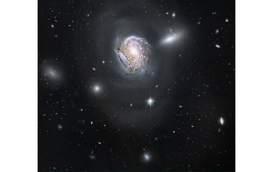 NGC 4911 in the constellation of Coma. See the interacting companions and the background objects. Credit: NASA (HST).