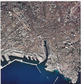 """Marsiglia città portuale in una foto aerea che mostra la città storica """"ricostruita"""" ed il porto storico riqualificato all'interno della nuova città con il nuovo grande porto costruito ad occidente (da materiali turistici 2010)."""