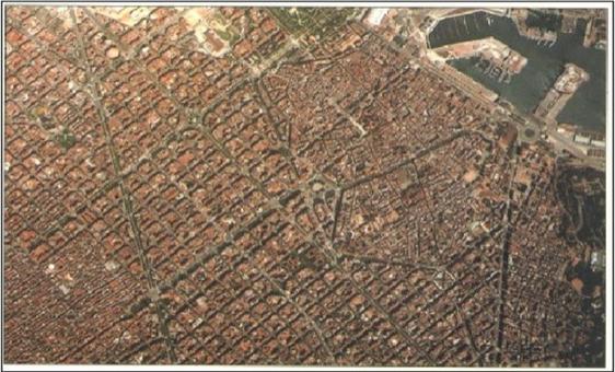 """Barcellona città portuale negli  anni '90 in una foto zenitale aerea che mostra con evidenza: la città storica, le Rambla lungo le antiche mura tre-quattrocentesche  e il quartiere del Raval anch'esso cinto da mura innanzi al porto. A confronto il tessuto regolare del grande ampliamento urbano del Cerdà:""""L'Example"""" e la """"Diagonal""""."""