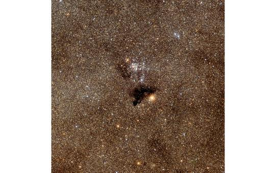 The dark object Barnard 86 against the background star cluster NGC 6520.