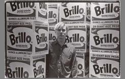 Andy Warhol con una delle sue opere legate al concetto di riproduzione seriale