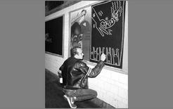 Keith Haring mentre realizza una delle sue opere nella metropolitana di New York