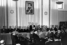 A Tel Aviv Ben Gurion annuncia la nascita di Israele. Sulla parete il ritratto di Theodor Herzl teorico del sionismo. Fonte: Wikipedia.